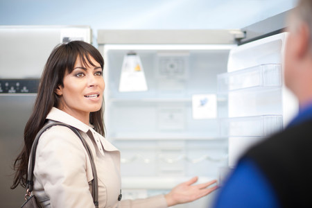 Woman looking at fridge in showroom