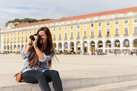 Young female tourist photographing in Rossio Square,Lisbon,Portugal LANG_EVOIMAGES