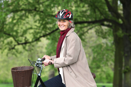 Senior woman riding bicycle in park,portrait
