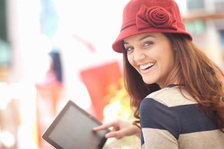 Woman in burgundy hat using digital tablet