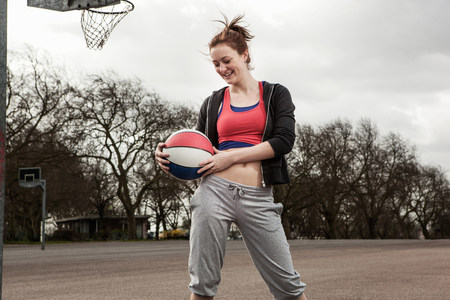 athleticism: Woman holding netball to waist LANG_EVOIMAGES