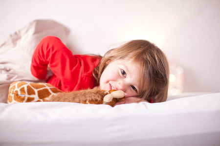 Young girl lying on bed with toy giraffe