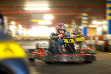 lighted: Young woman racing on go cart track