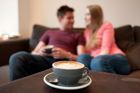 Young couple lounging on sofa in cafe LANG_EVOIMAGES