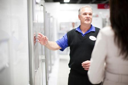 Woman looking at refrigerator in showroom