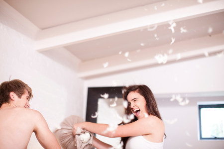 jesting: Young couple having a pillow fight LANG_EVOIMAGES
