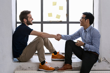 Two young male creatives shaking hands
