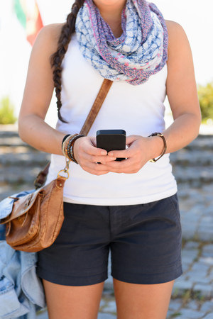 Close up of young female standing in street using smartphone LANG_EVOIMAGES