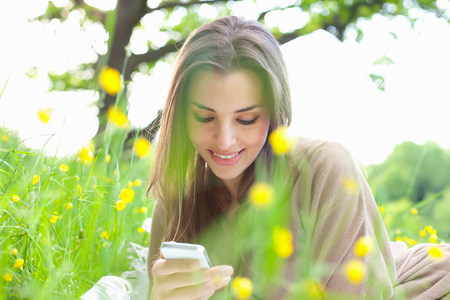untruth: Close up of young woman in field looking at mobile