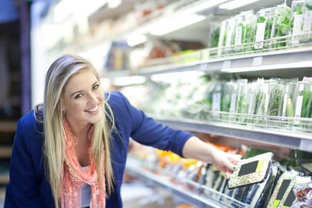 commodities: Mujeres jóvenes que miran hierbas en supermercado