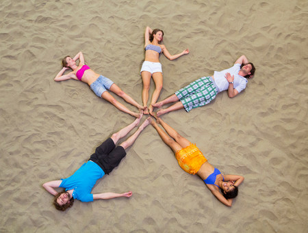bikini top: Aerial view of friends lying in star shape on sand
