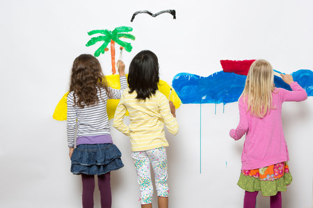 Three girls painting ocean and island on wall