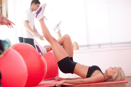 Young woman on gym floor training with exercise balls LANG_EVOIMAGES