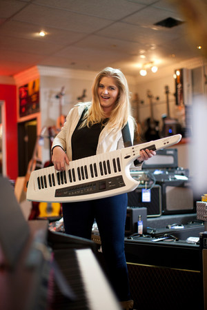 decide deciding: Young woman playing keytar in music store