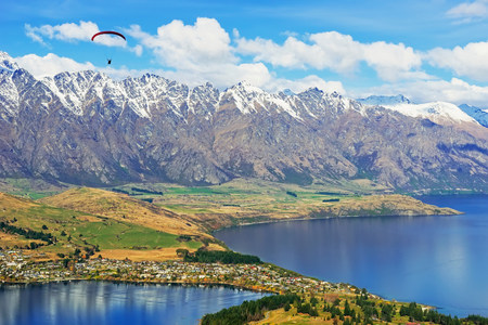 urban idyll: Paragliding over Remarkables Mountain Range,Queenstown,South Island,New Zealand LANG_EVOIMAGES