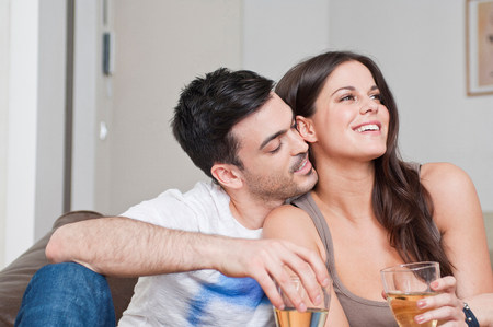 parlours: Young couple sitting on sofa sharing glass of wine LANG_EVOIMAGES