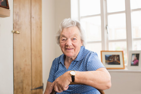 70 75: Senior adult woman sitting in room LANG_EVOIMAGES