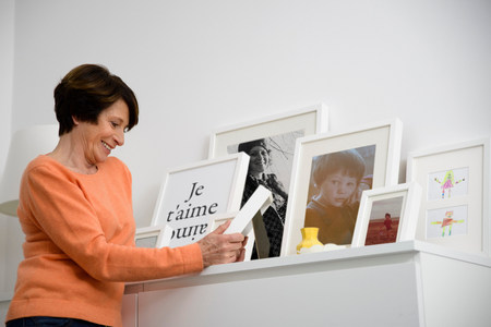 parlours: Senior woman looking at family photographs LANG_EVOIMAGES