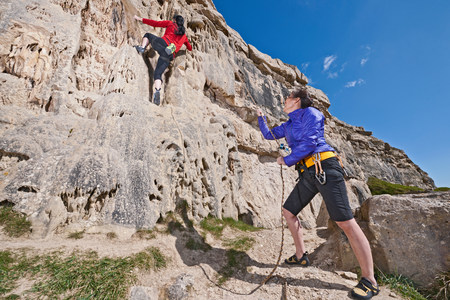 Female rock climbers near cliff base