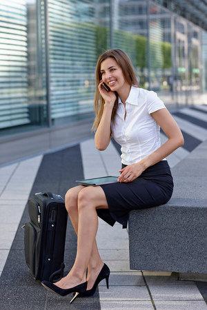 Young businesswoman sitting and using mobile phone,smiling