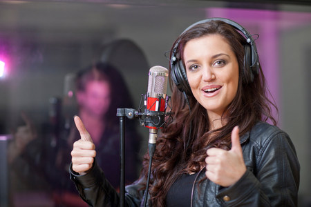 earbud: Female singer in recording studio LANG_EVOIMAGES