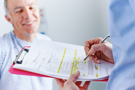 Nurse completing paperwork,patient in background LANG_EVOIMAGES