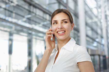 Young businesswoman using mobile phone,smiling