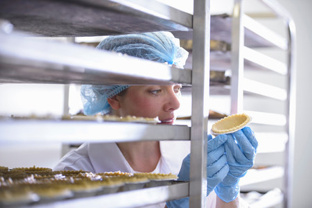35 to 40 year olds: Baker inspecting freshly baked pie case LANG_EVOIMAGES