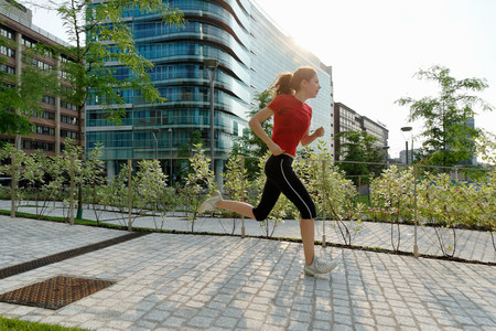 impulsive: Young woman running past office buildings