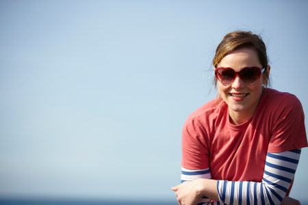 Portrait of young woman wearing heart shape sunglasses at coast