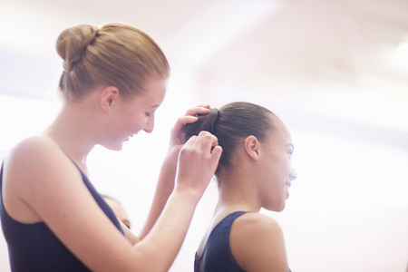 off shoulder: Teenage ballerina helping friend with hair LANG_EVOIMAGES