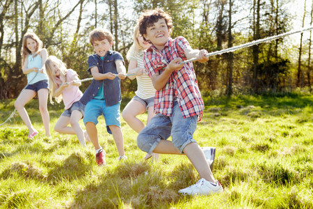 level playing field: Group of young children playing tug o war LANG_EVOIMAGES