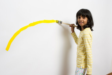Portrait of girl painting yellow curve on wall