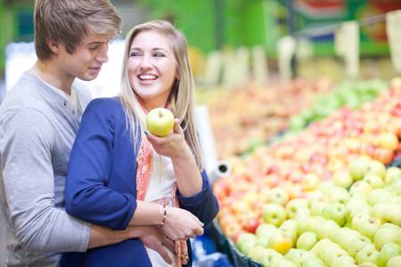 commodities: Pareja joven comprando frutas en el mercado interior LANG_EVOIMAGES