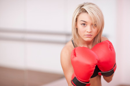 Portrait of young woman in boxing gloves