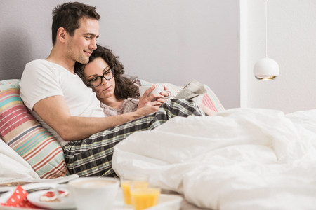 Mid adult couple reading newspaper in bed LANG_EVOIMAGES