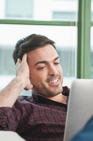 parlours: Close up of young man at home using digital tablet