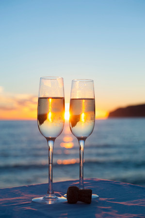 Two wine glasses with sea in background