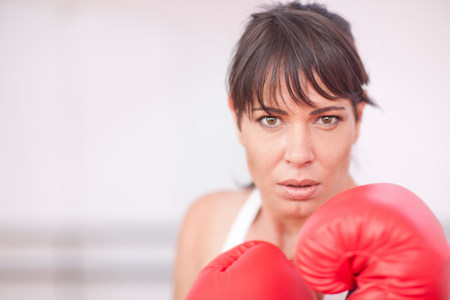 Portrait of mid adult woman in boxing gloves LANG_EVOIMAGES