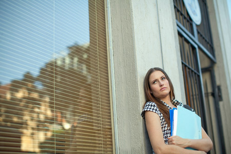 mirroring: Unhappy young woman holding files outside city office