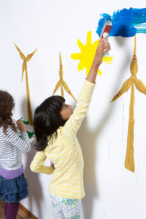 well behaved: Two girls painting wind turbines on wall LANG_EVOIMAGES