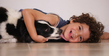 pooches: Young boy lying on floor hugging his pet dog