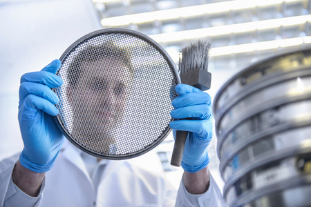 gifted: Portrait of scientist holding metal brush and sieve
