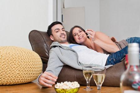 sleeveless hoodie: Young couple lying on sofa sharing wine and popcorn