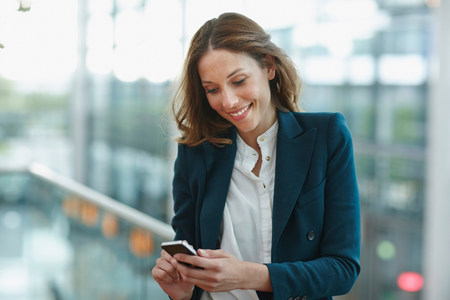 Young business woman outside office buildings using smartphone