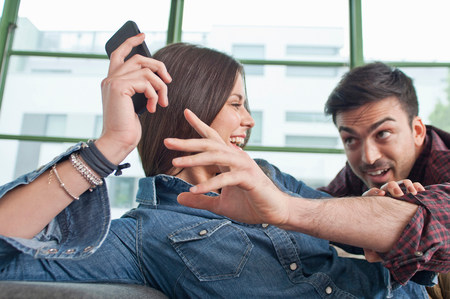 jesting: Young couple at home fooling about with mobile phone