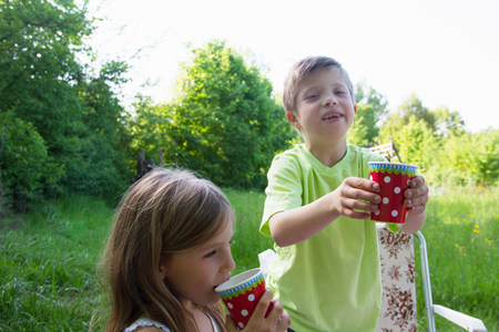 Brother and sister with picnic cups LANG_EVOIMAGES
