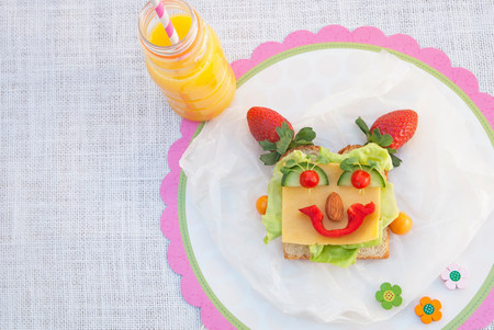 Face made from fresh food on slice of bread