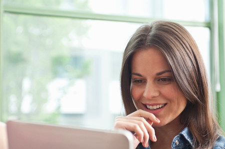 good color: Young woman looking at digital tablet