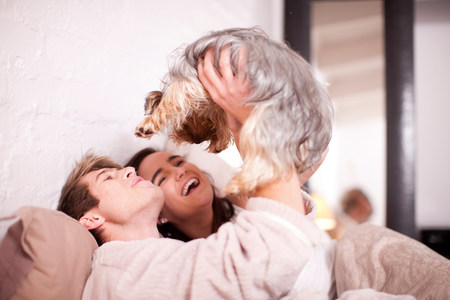 Young couple in bed with pet dog LANG_EVOIMAGES